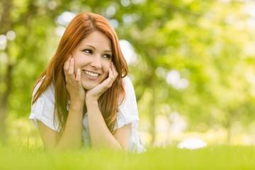 Portrait of a pretty redhead happy and lying