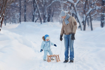 Child sits on the sledge, His Father waits