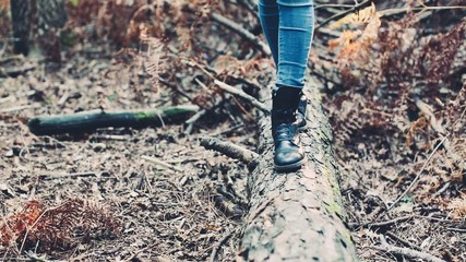 Girl walking on a fallen trunk