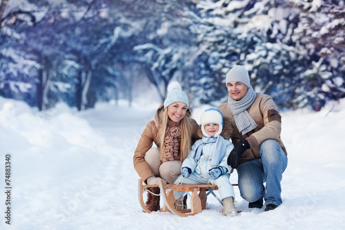 Leinwanddruck Bild Portrait of Young family in a winter park
