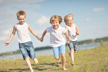 three children playing on meadow in summer