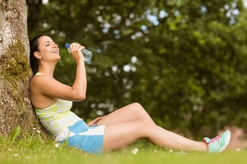Fit brunette sitting against tree drinking water
