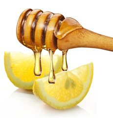 Honey with wood stick pouring onto a slice of lemon.