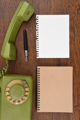 Vintage rotary telephone and pen with notebook.