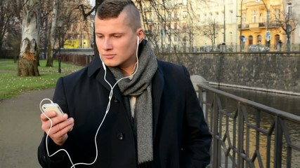 man walking and listens music on smartphone-city