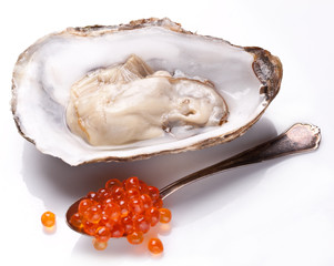Fresh opened oyster and silver spoon full of caviar.