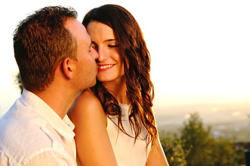 Romantic young couple will kiss at sunset