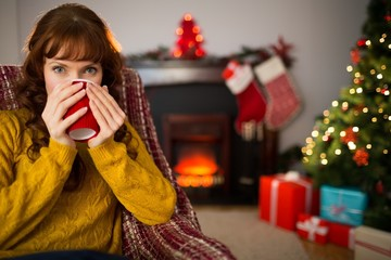Cheerful redhead drinking hot drink at christmas