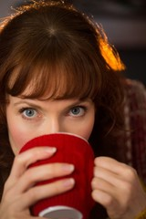 Portrait of redhead drinking hot drink at christmas