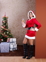 Young woman dressed in Mama Claus with a glass of champagne.