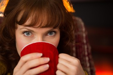 Portrait of beauty redhead drinking hot drink at christmas