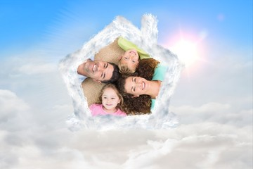 Composite image of happy family lying on the rug in a circle