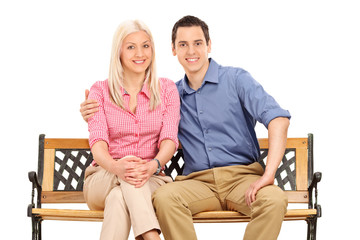 Cheerful young couple posing seated on a bench