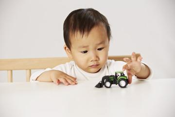 Kind spielt mit Spielzeugtraktor 1