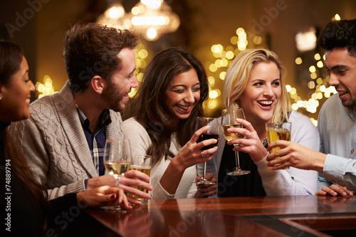 Group Of Friends Enjoying Evening Drinks In Bar - 74889794