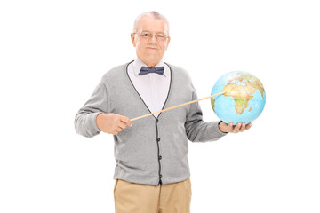 Mature teacher pointing on a globe with a stick