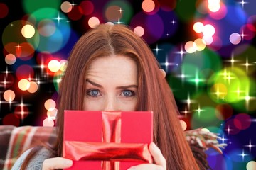 Composite image of woman holding gift