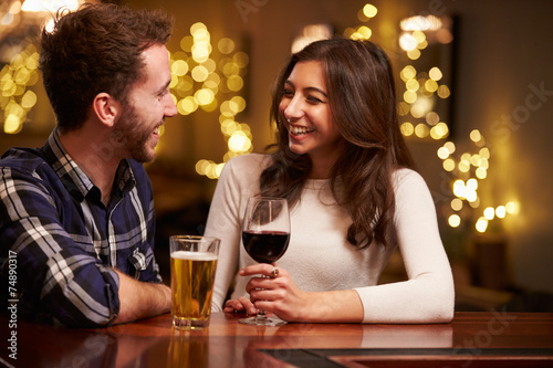 Couple Enjoying Evening Drinks In Bar - 74890317