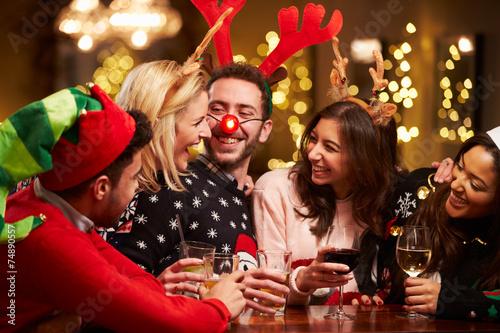 Leinwanddruck Bild Group Of Friends Enjoying Christmas Drinks In Bar