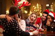 Couple Kissing In Bar As Friends Enjoy Christmas Drinks - 74890750