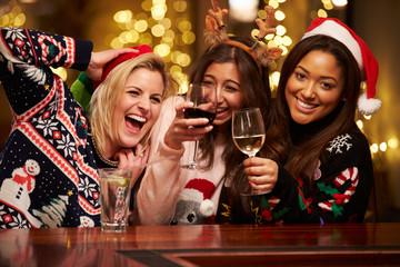 Group Of Female Friends Enjoying Christmas Drinks In Bar