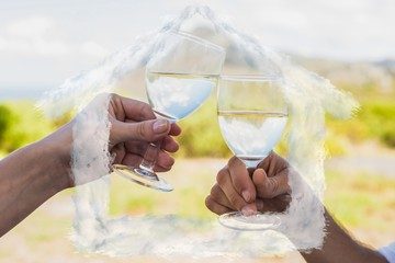 Composite image of couple clinking wine glasses outside
