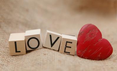 mot love sur cubes en bois et coeur rouge