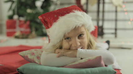 Adorable little girl blonde lies on the pillow in Santa's hat