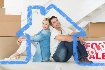 Composite image of smiling couple with boxes in a new house
