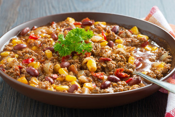 Mexican dish chili con carne in a brown pottery plate, close-up