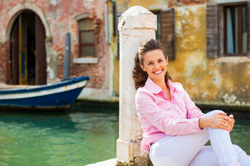 Portrait of smiling young woman sitting on street in venice