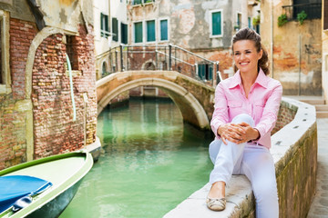 Happy young woman sitting on bridge in venice, italy