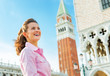 Happy young woman against campanile di san marco in venice