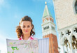 Young woman looking at map against campanile di san marco