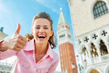 Happy woman against campanile di san marco showing thumbs up
