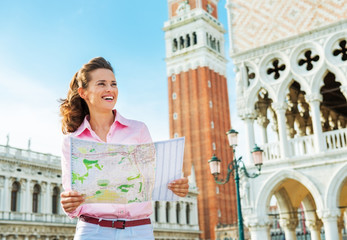 Happy young woman looking at map against campanile di san marco