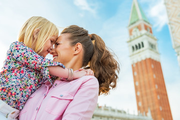 Portrait of mother and baby hugging near campanile di san marco