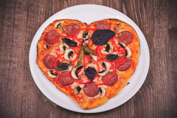 heart shaped pizza on white plate