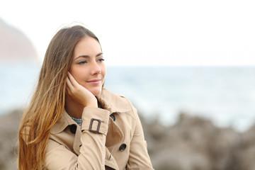 Beautiful melancholic woman thinking in winter on the beach