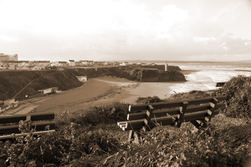 benches on a cliff edge  with views of Ballybunion in sepia