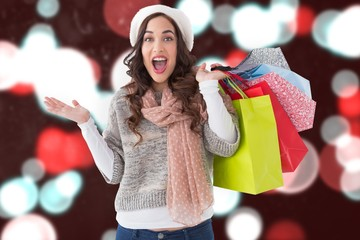 Composite image of excited brunette with shopping bags