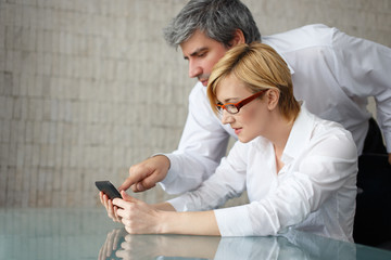Young businesspeople in office watching financial data on tablet