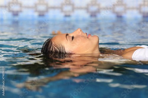 Leinwanddruck Bild Profile of a beauty relaxed woman face floating in water