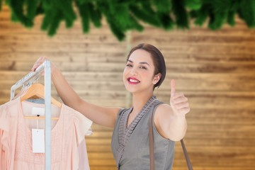 Composite image of smiling woman giving thumbs up