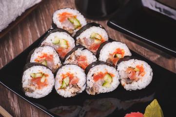 assorti fish sushi roll on black plate