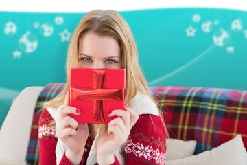 Composite image of blonde holding a christmas gift