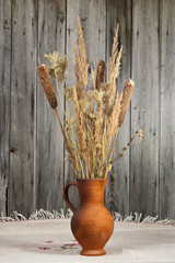 Clay jug with a bouquet on old wooden background