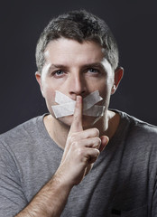 attractive man mouth sealed on tape hush not speaking concept