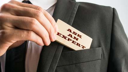 Businessman showing a wooden card reading Ask an expert