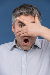 Attractive man covering eyes with his hand.